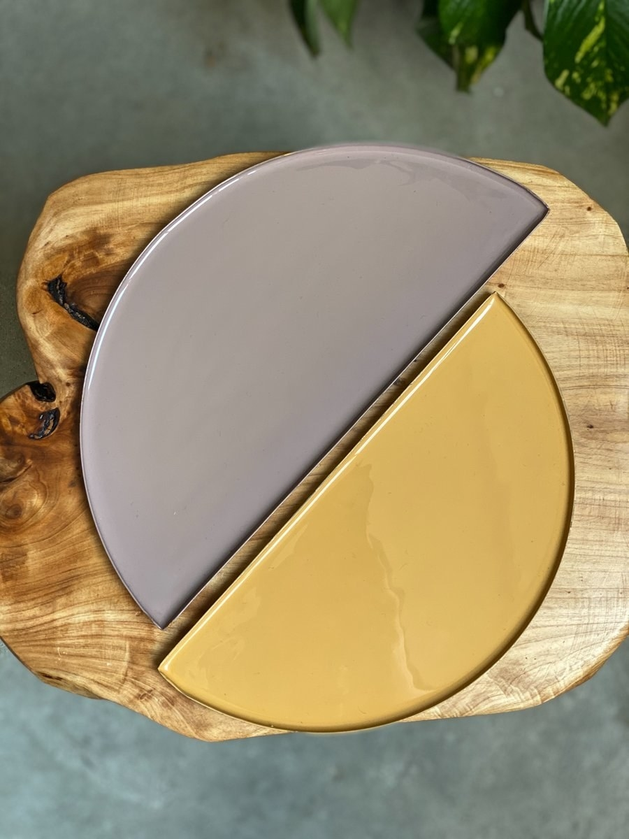 Two semi-circle trays next to each other, one in grey and one in gold