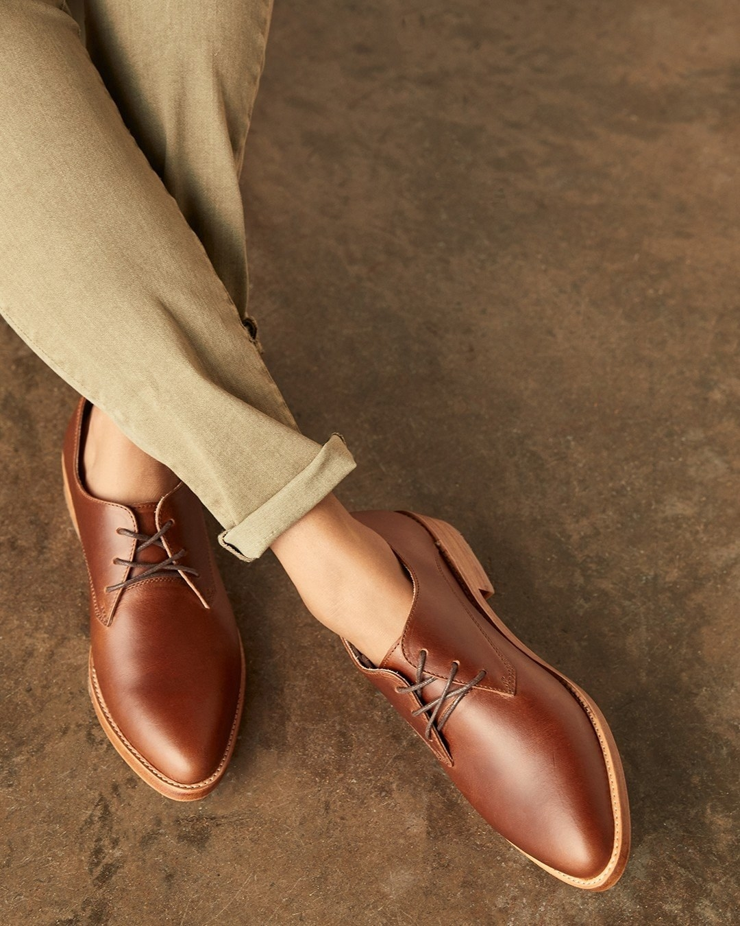 Nisolo's brown Oxfords paired with rolled up pants