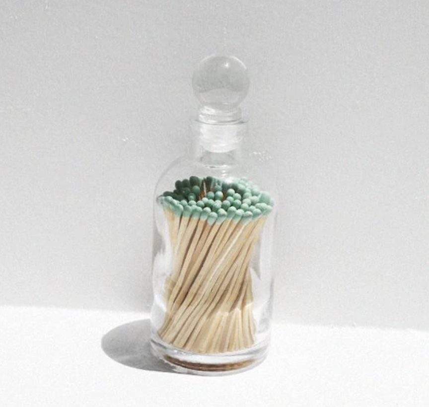 A clear glass case with matches inside with teal heads