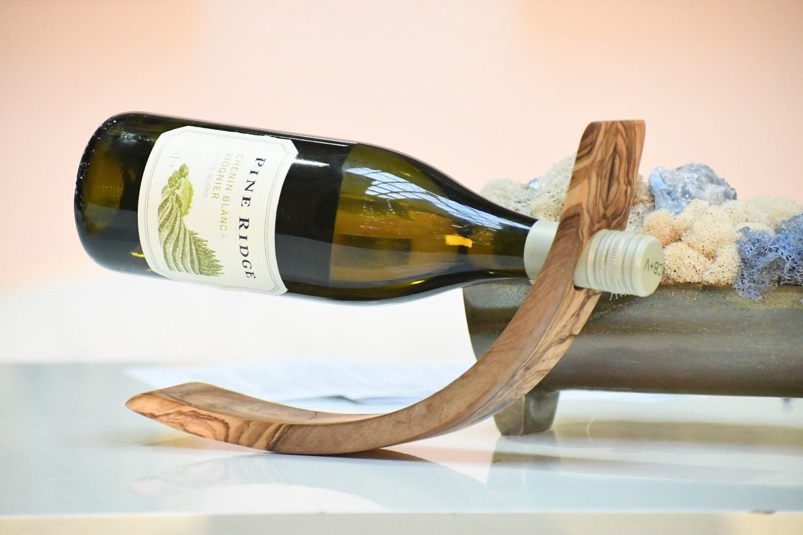 Wood curved stick with a hole in the top with a wine bottle being held up in the air