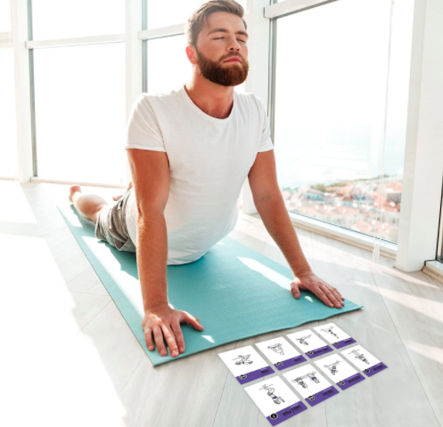 Model moves to Cobra on a blue mat next to white and purple yoga cards with various poses