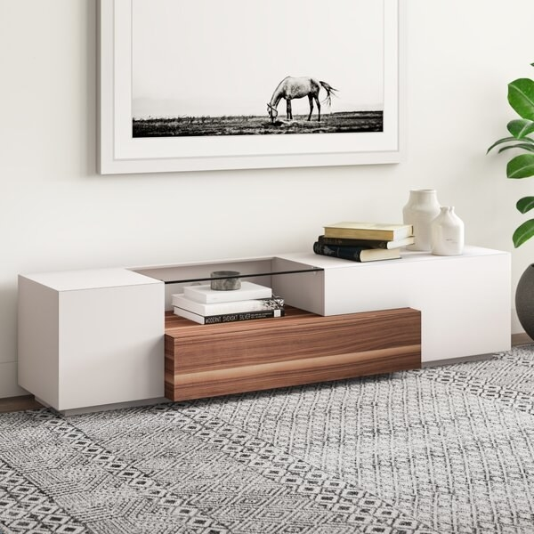 Long white stand with an asymmetrical glass shelf and wood center shelf