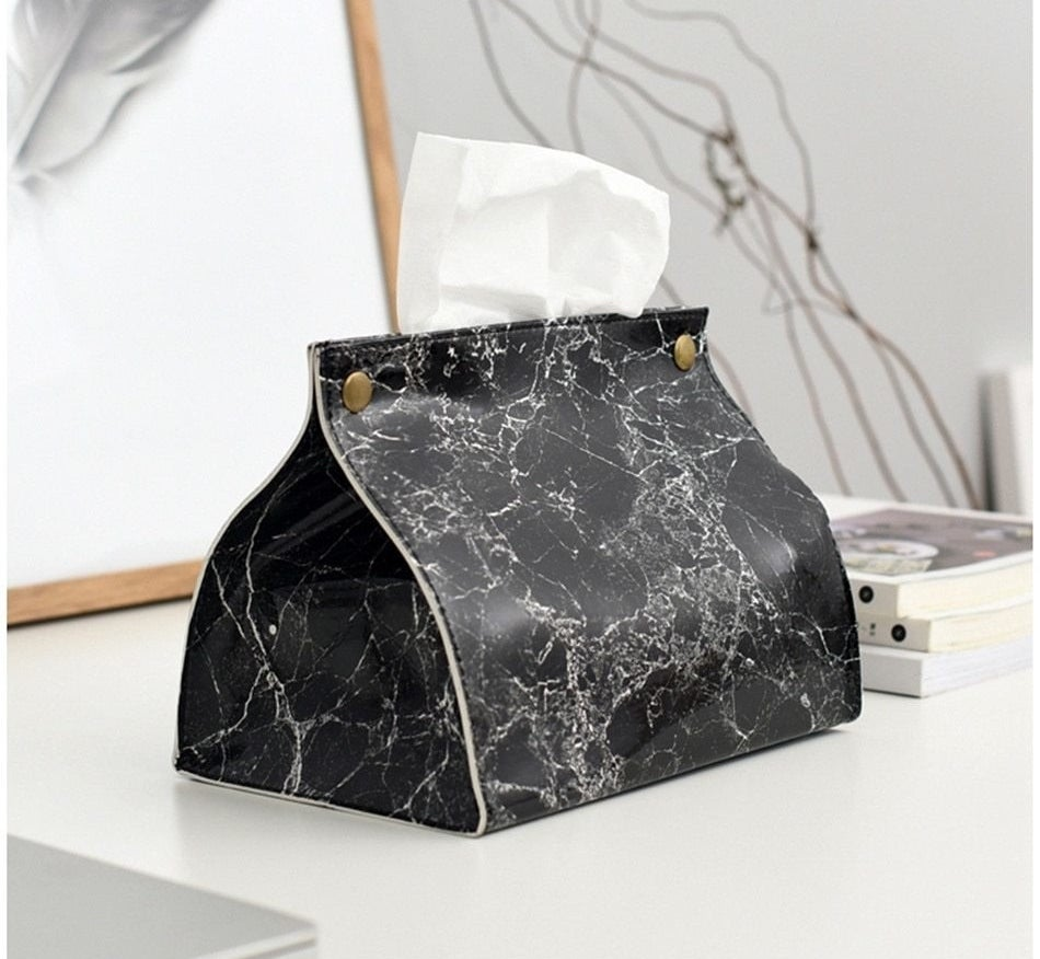 A black marble leather tissue box cover with gold hardware and a tissue coming out of the top