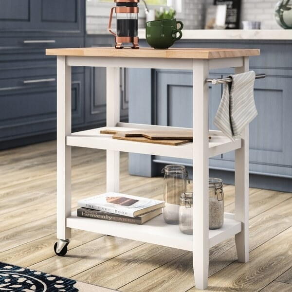 White and natural wood top cart with wheels on one side, two shelves, countertop, and a towel rack
