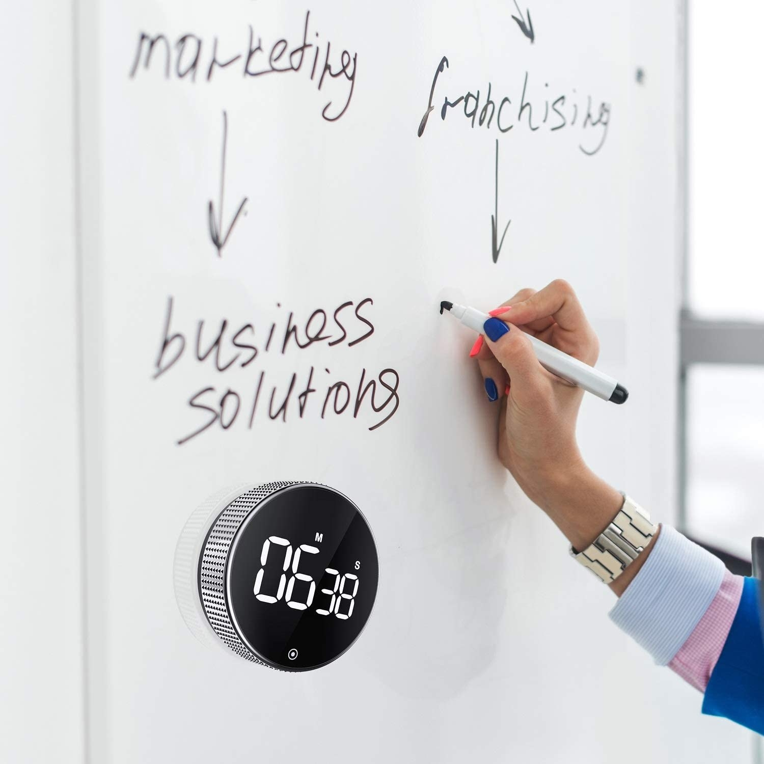 A person writing on a blackboard that has the timer attached to it