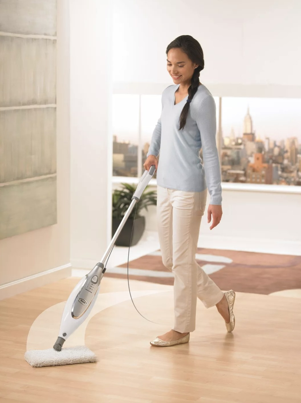 A model pushing a white steam mop across her wood floors