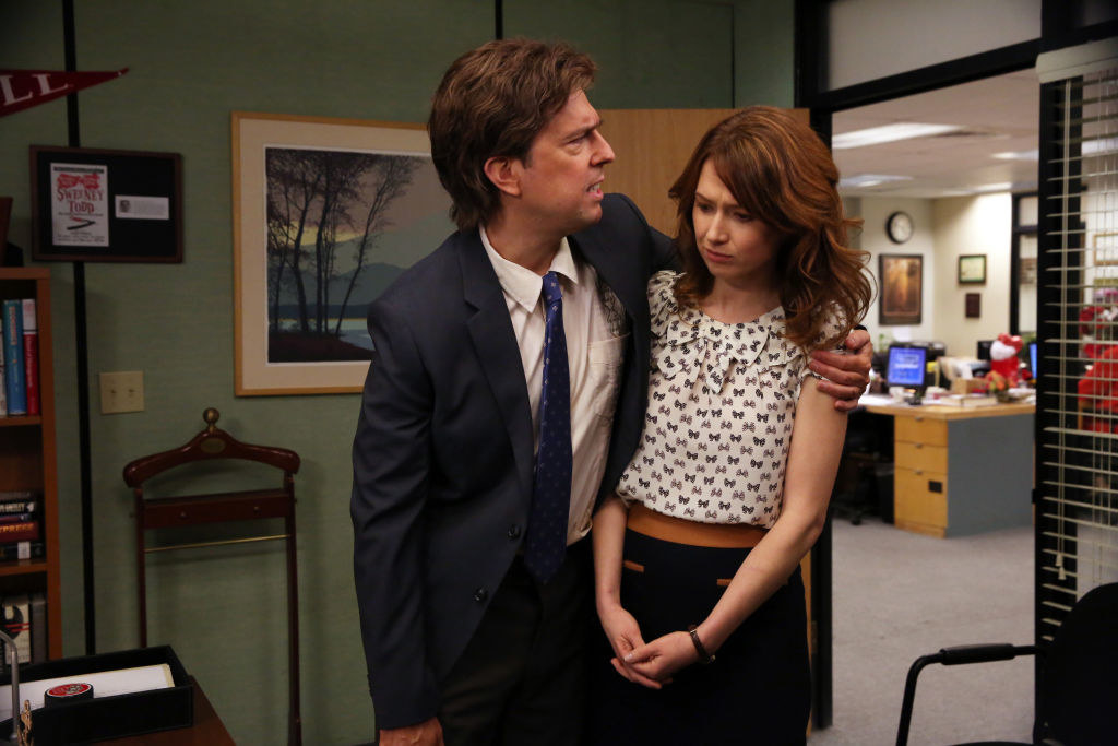 """Ed Helmms hugs Ellie Kemper's character uncomfortably in a scene from """"The Office"""""""