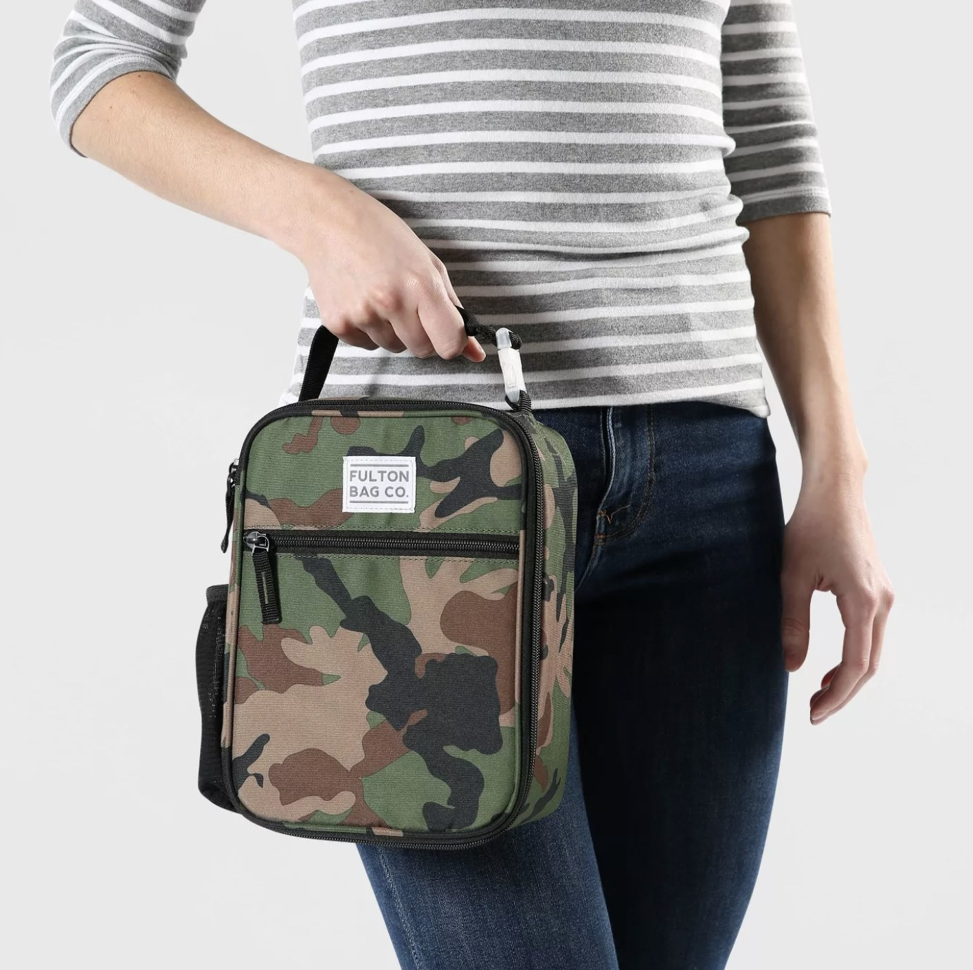 A model holding a camo lunchbox that has an exterior zipper pocket and a water bottle pocket