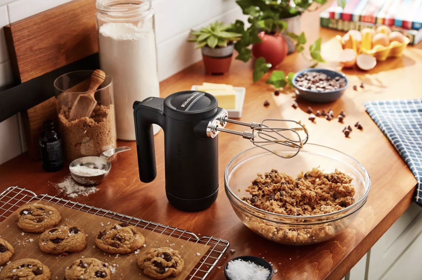 A black, KitchenAid hand mixer surrounded by baking supplies and chocolate chip cookies