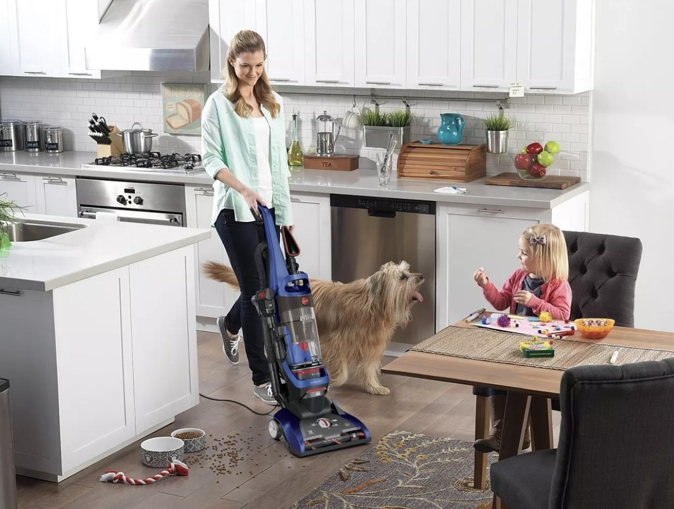 A woman using a vacuum to clean dog food off of her kitchen floor