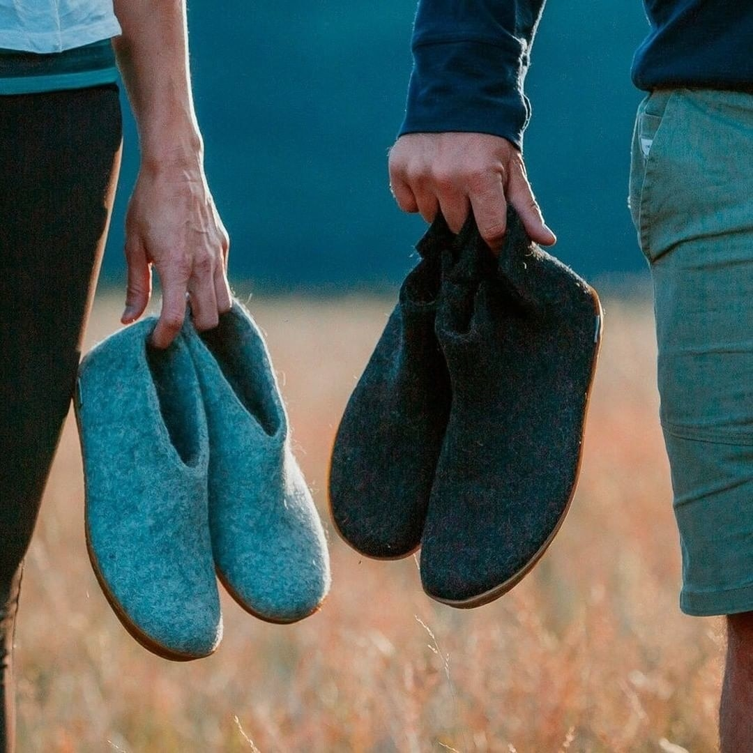 two models holding the shoes at the tips of their fingers in a field