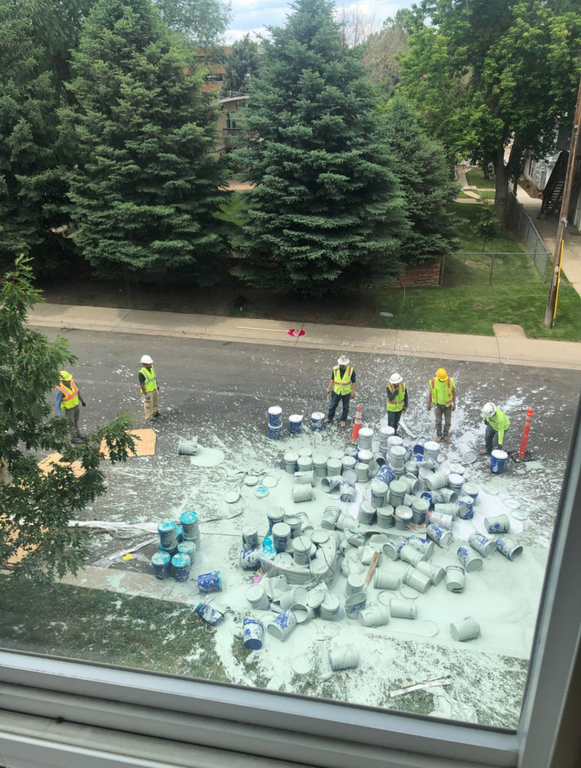 painters stand around a huge amount of spilled paint