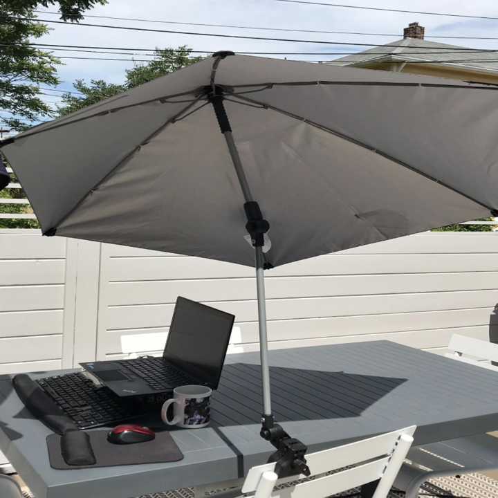 A white umbrella attached to a chair shading a laptop on a table
