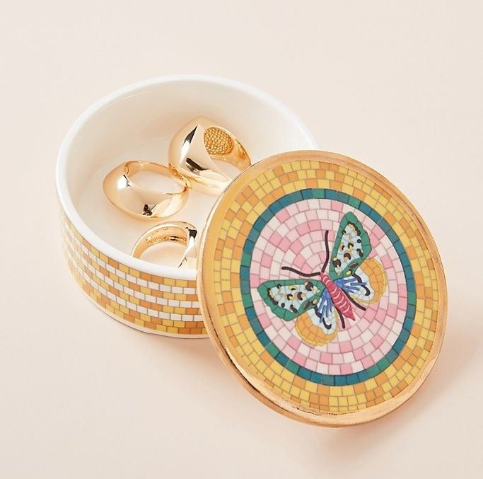 Small circular dish with a lid that has a mosaic-like pattern on it in yellow with a butterfly in a pink circle on top