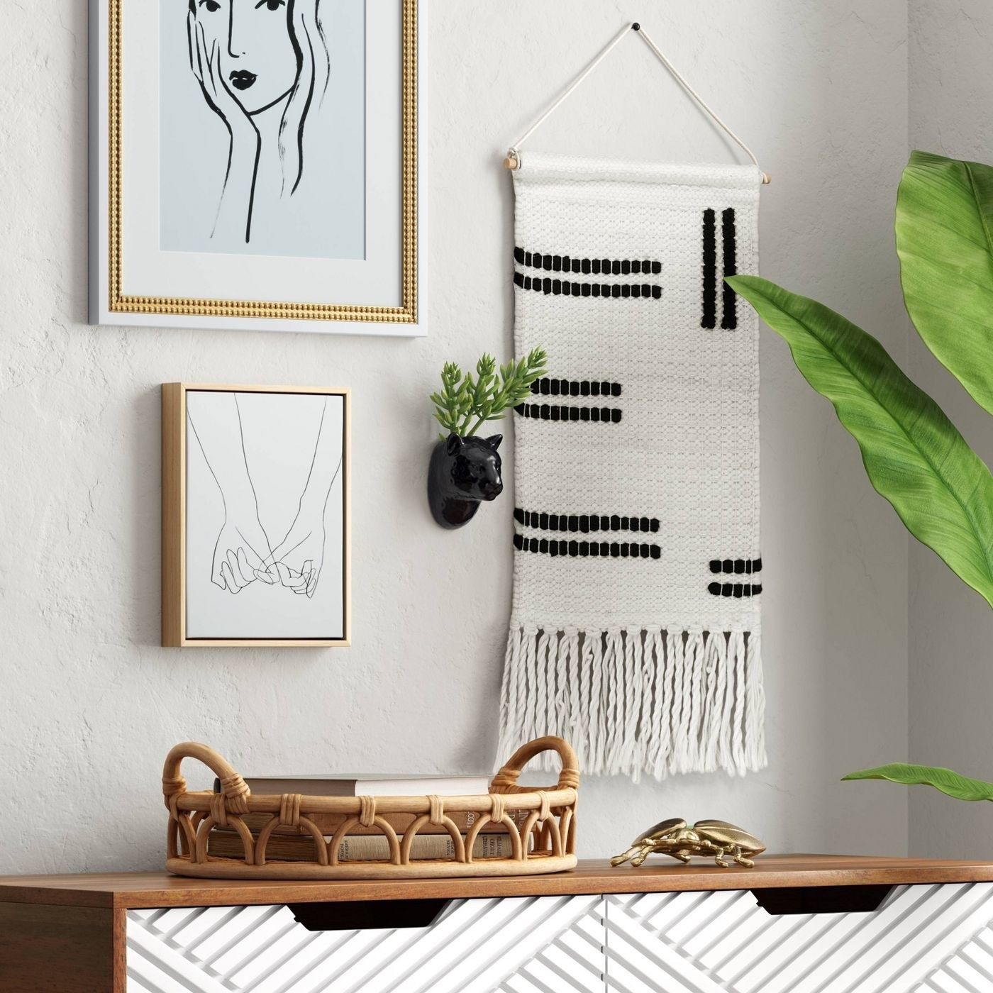 White woven wall hanging with black vertical and horizontal stripes and fringe at the bottom