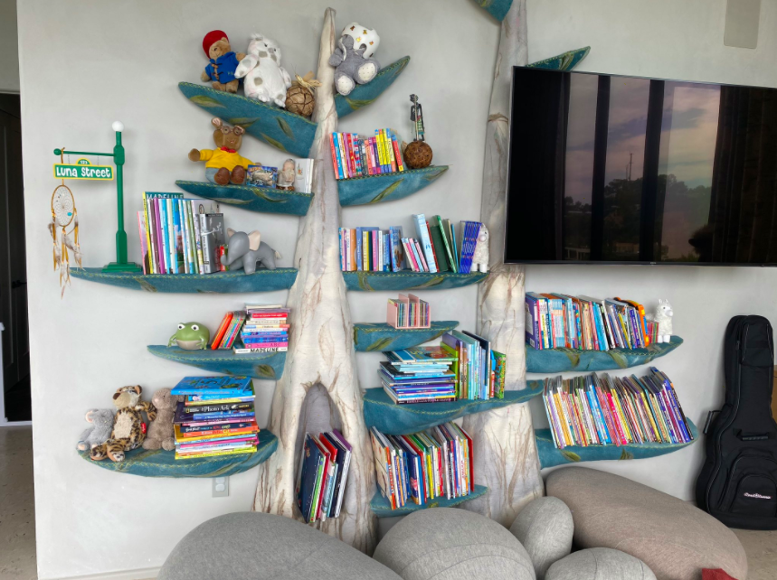 "wall of books with an ""Arthur"" plushie"