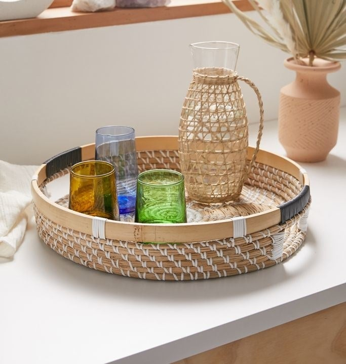 Woven seagrass serving tray with cutout side handles and assorted glasses in it