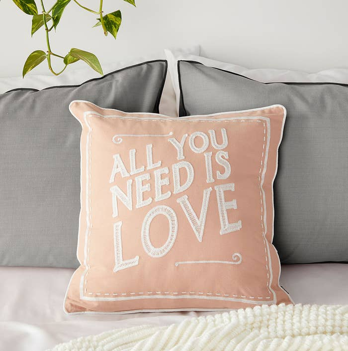 A cushion that reads All You Need Is Love