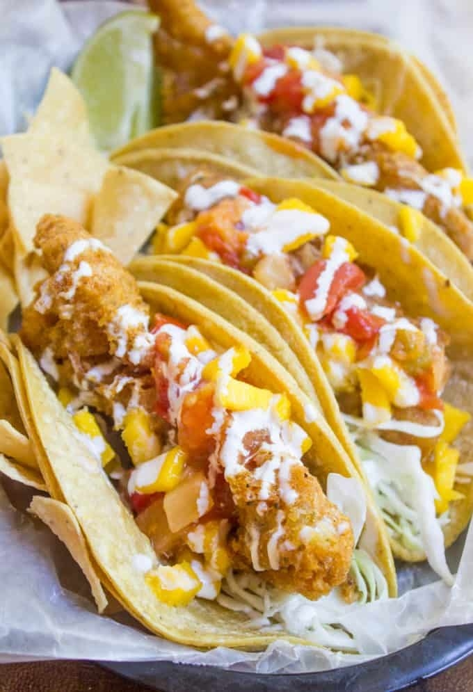 Three crispy fish tacos in tortillas with cabbage, mango and tomato salsa, and crema on top.