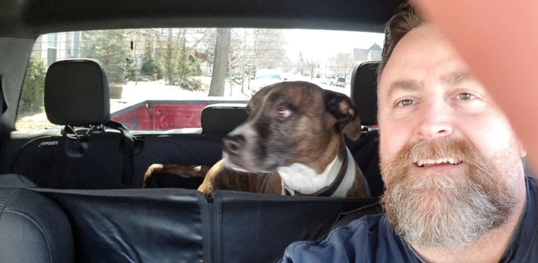Man posing with dog in covered back seat