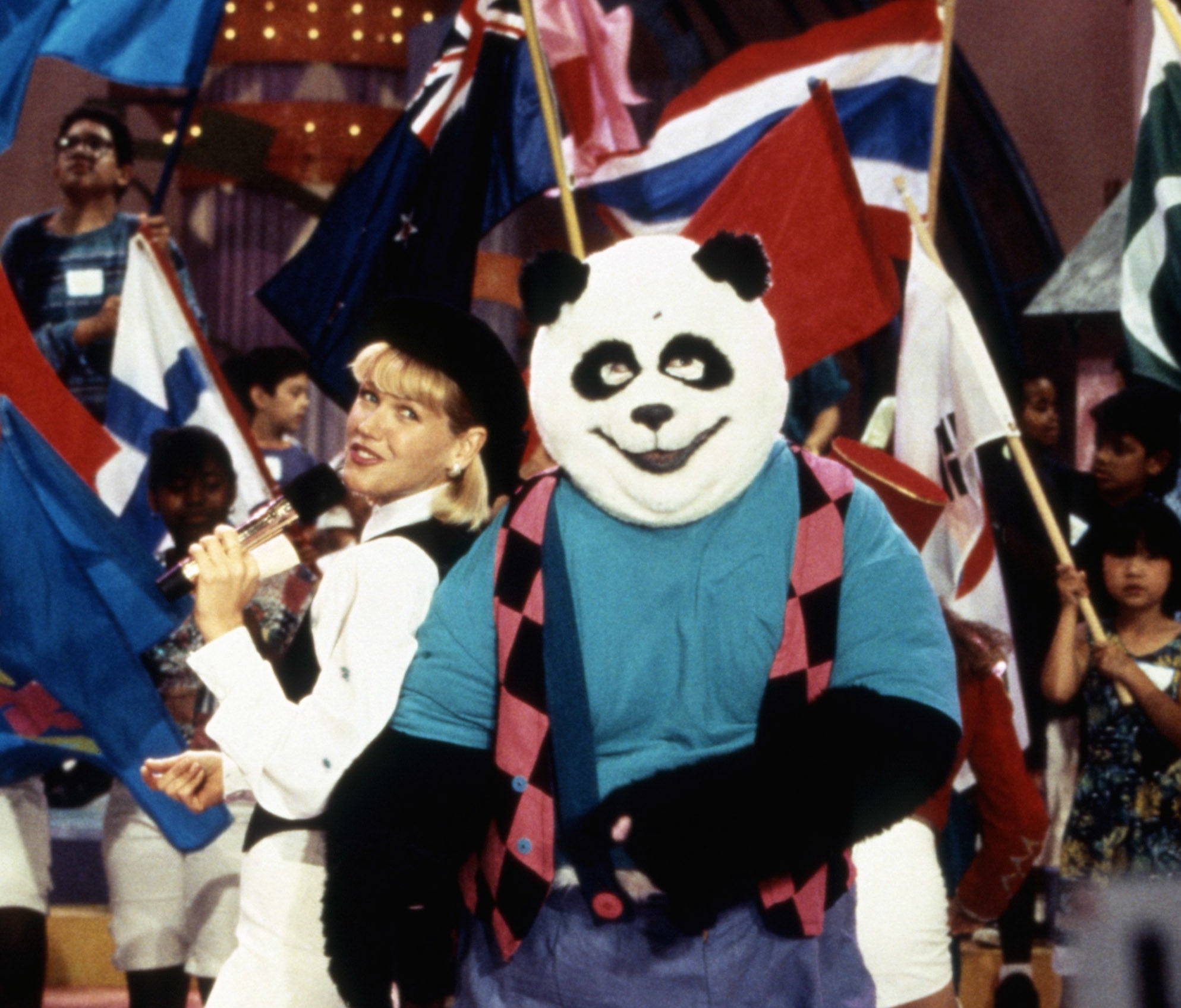 Xuxa standing next to a man in a Panda costume wearing human clothes