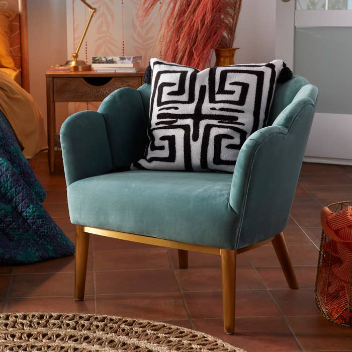 The teal accent chair with scalloped back