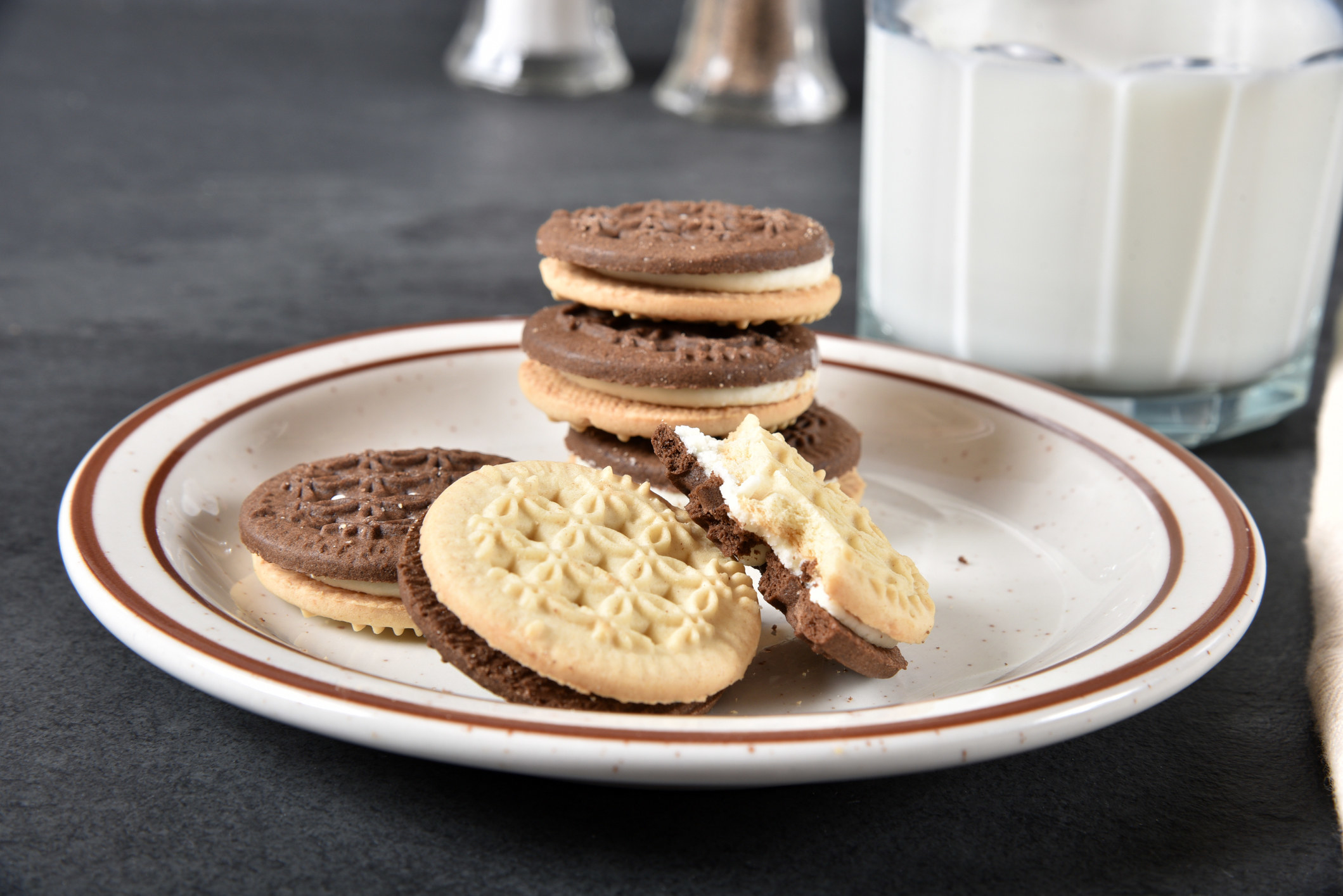 A stack of vanilla and chocolate sandwich cookies on plate next to a glass of milk