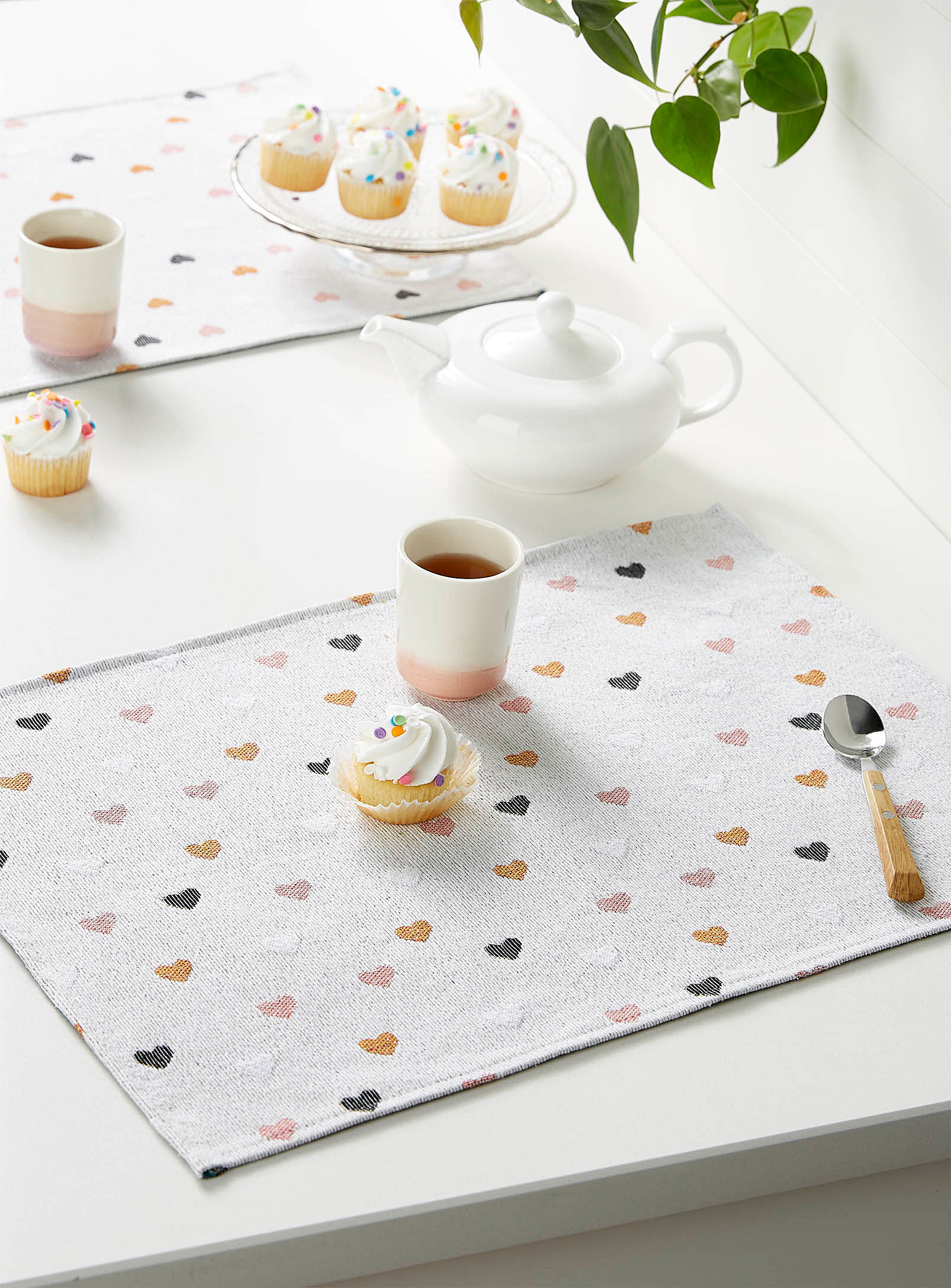 A rectangular cloth placemat on a table with a cupcake, a cup and a spoon on it