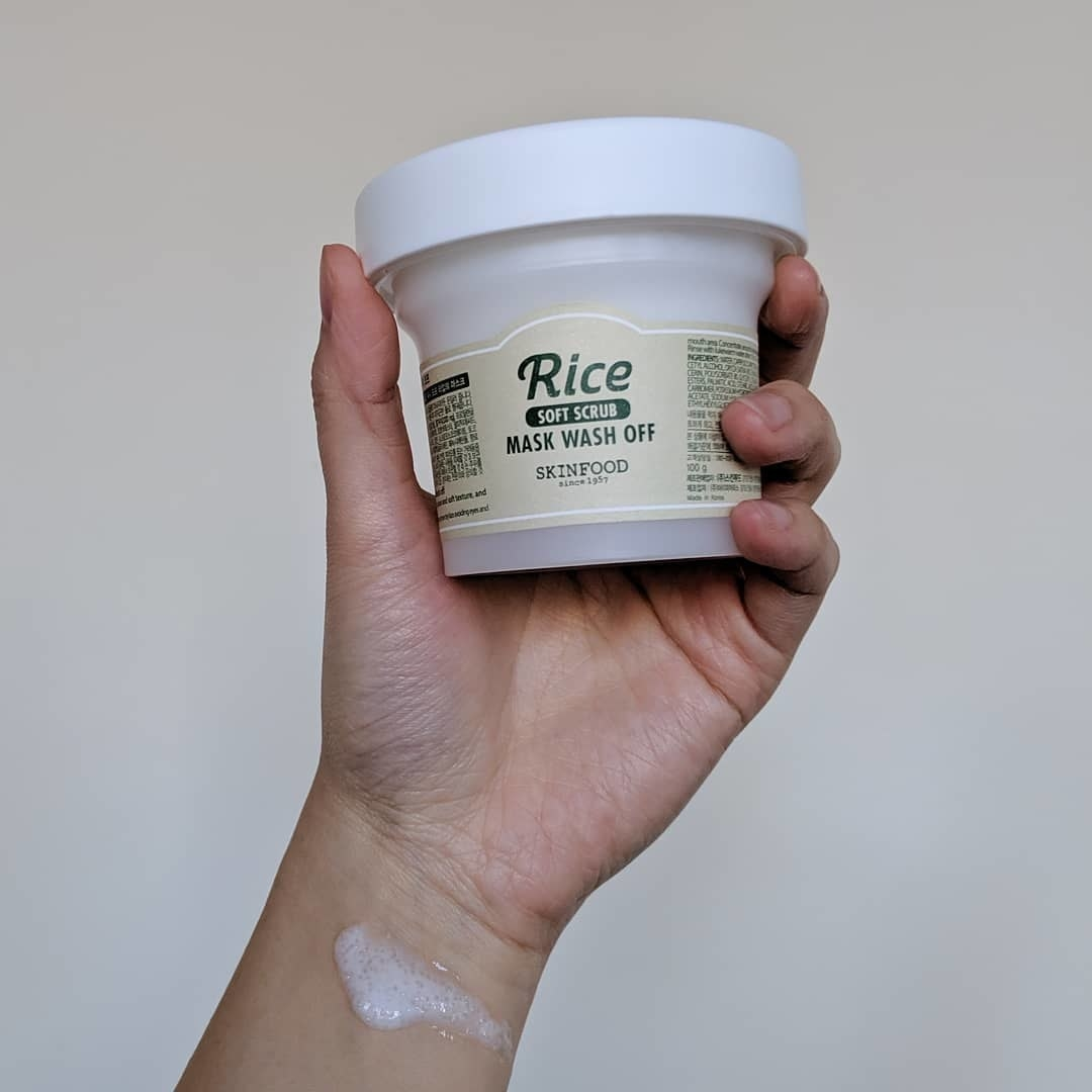 A person holds up the tub of the rice mask