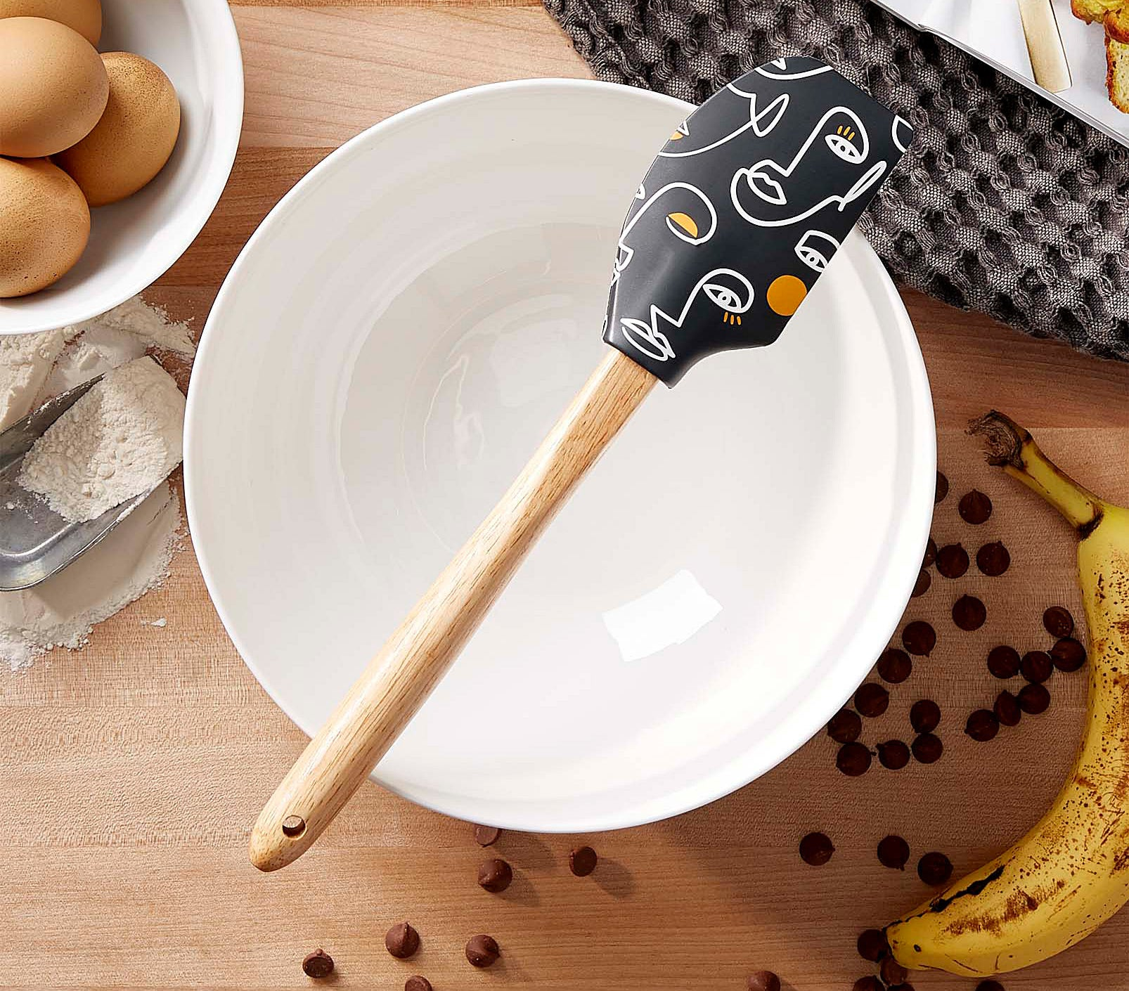 A spatula sitting on top of a large empty mixing bowl
