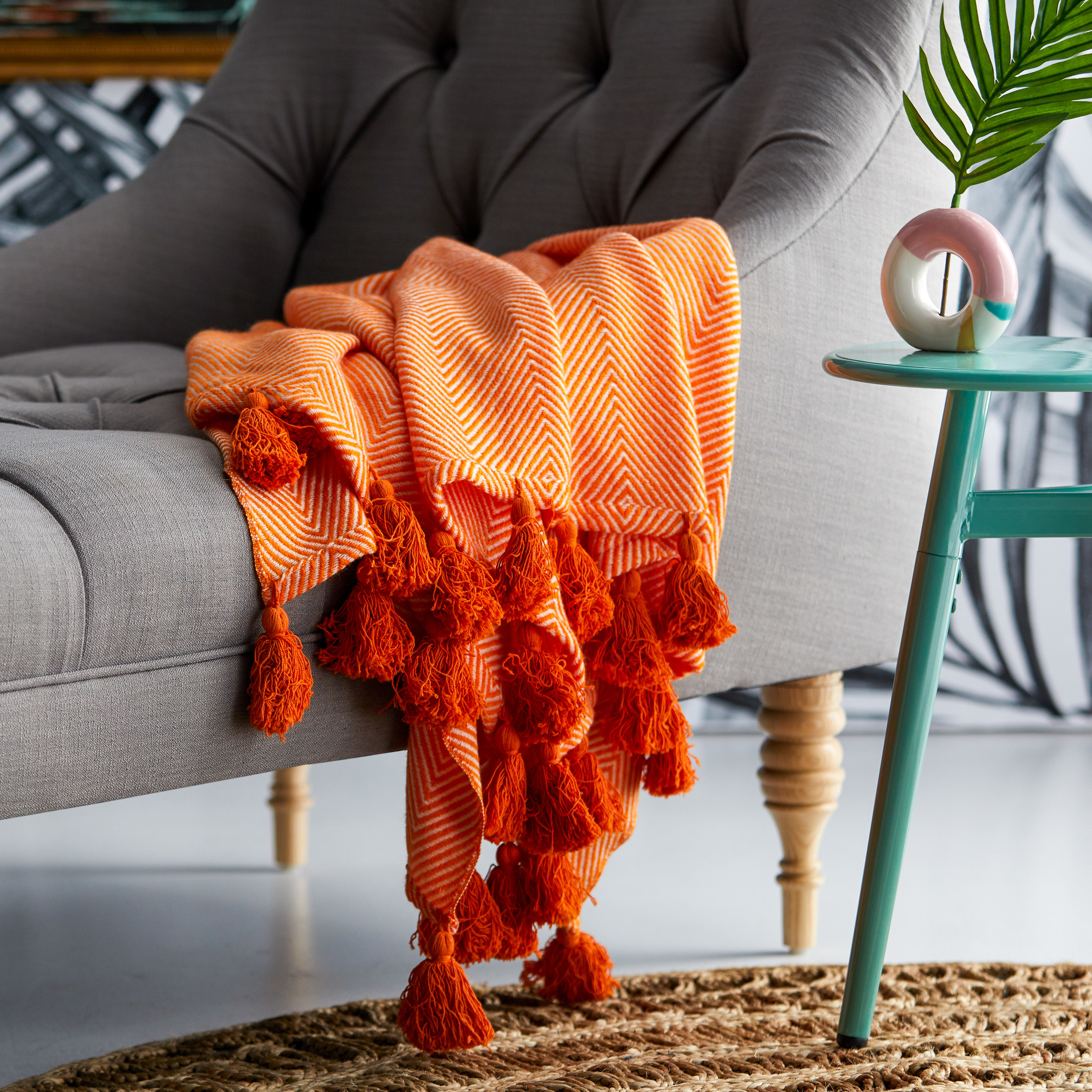 Bright orange blanket with a chevron pattern and large fringe tassels on the ends