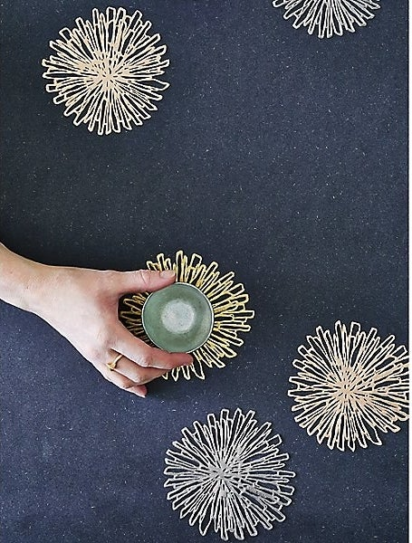 Four gold flower-like coasters with a hand setting a small glass on one