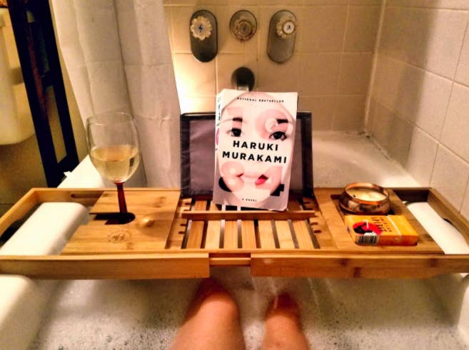 Reviewer's light wood bath caddy with a glass of white wine, a book, and candle over their bath tub