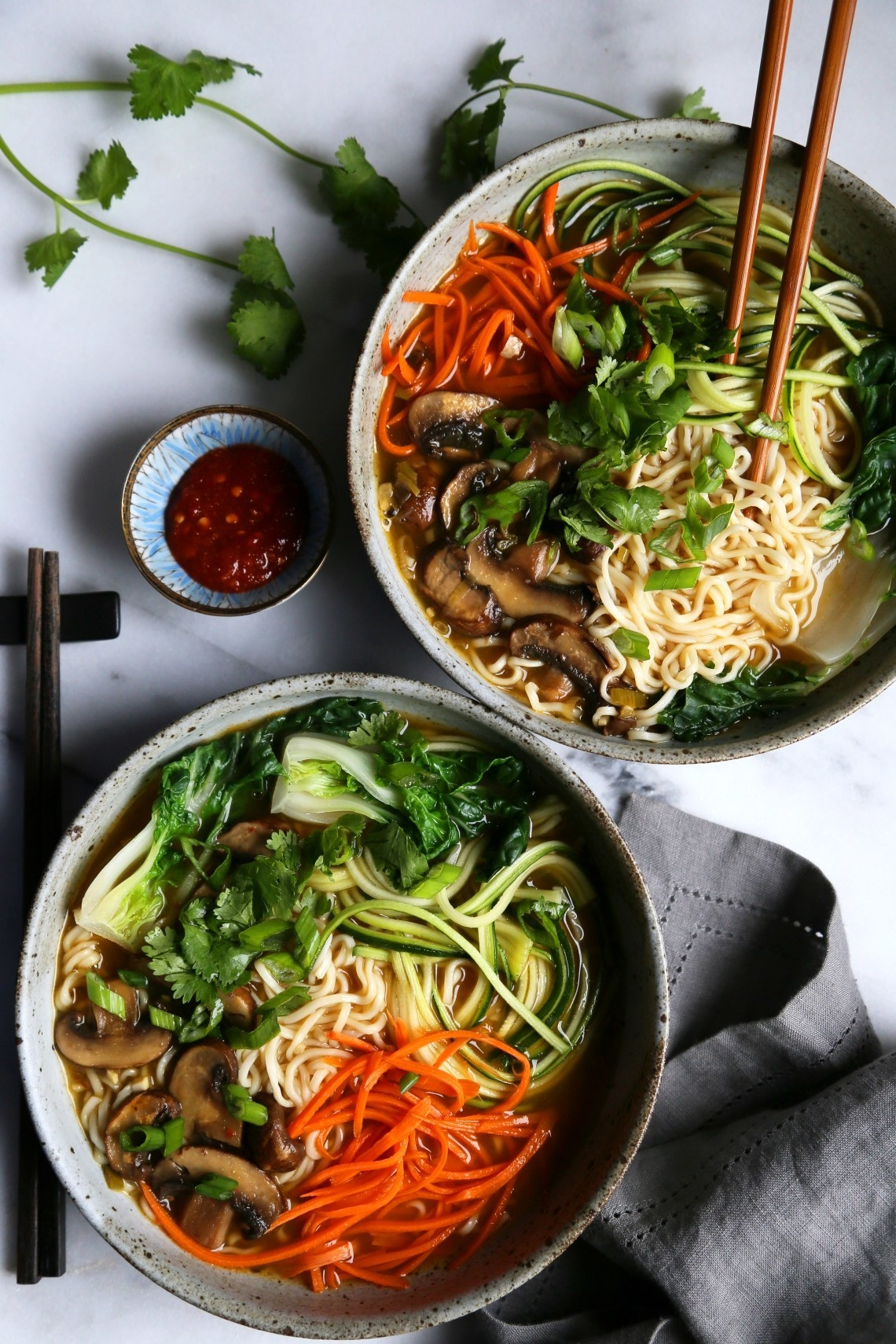 Two bowls of ramen soup with mushrooms, zucchini, carrots, bok choy, and cilantro.