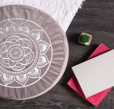Gray and white circular meditation pillow on hardwood floor next to journal