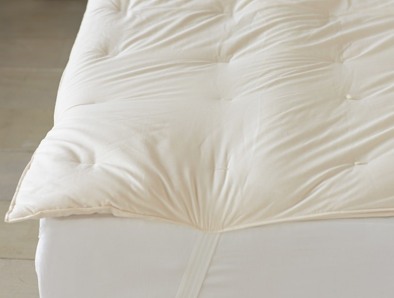 The off-white topper on a bed, secured under the mattress by elastic corner straps