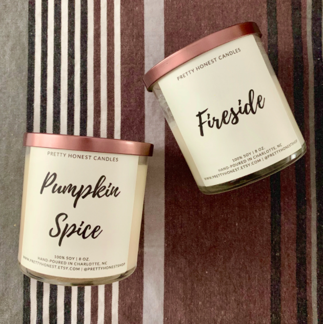 """Hand-poured soy candles that say """"Pumpkin Spice"""" and """"Fireside"""" in front of a striped carpet"""