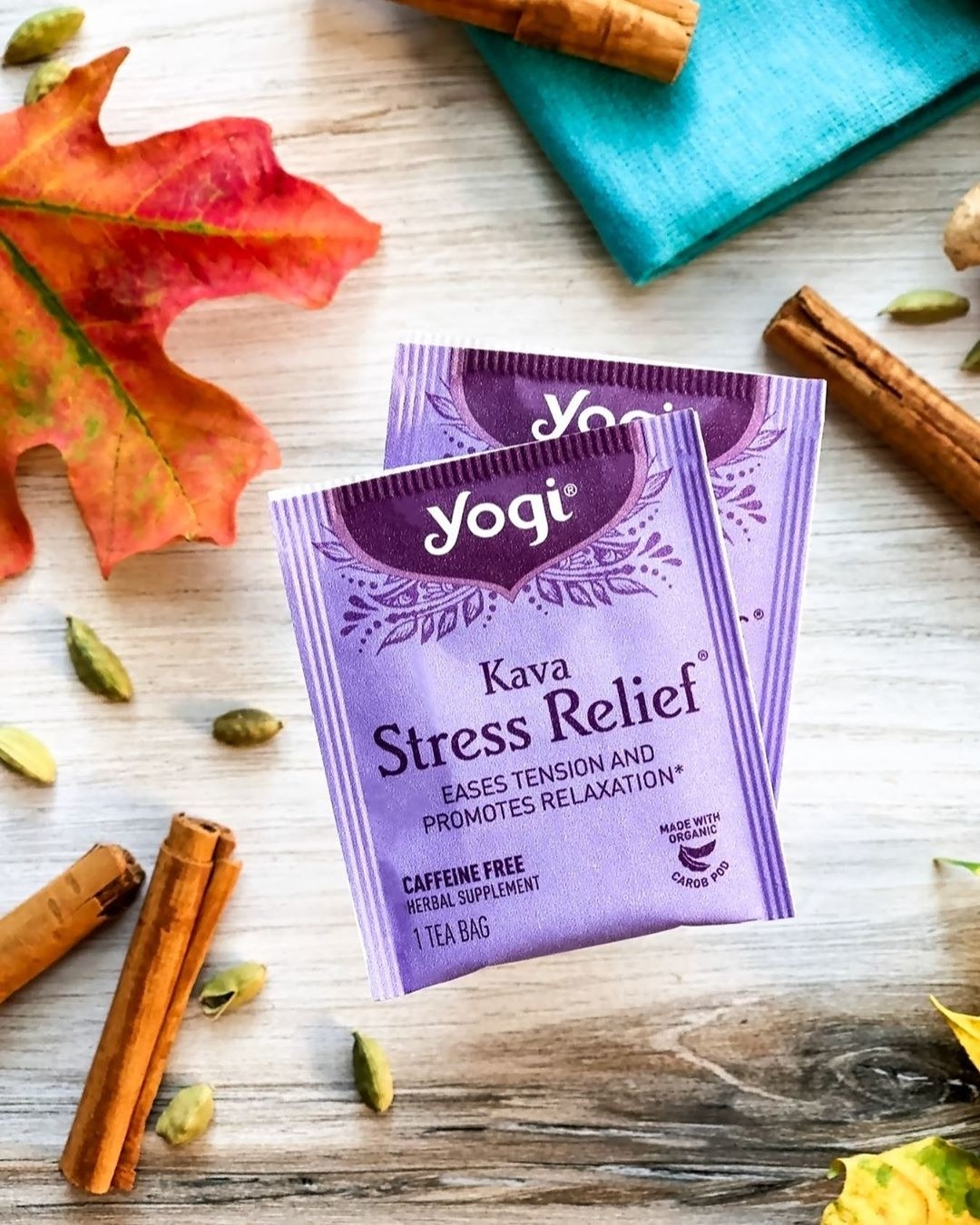 """Purple tea bags that say """"Yogi Kava Stress Relief"""" on a wooden table with cinnamon sticks"""