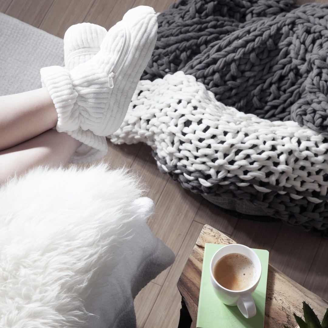 A person reclines on a comfy sofa while wearing the booties
