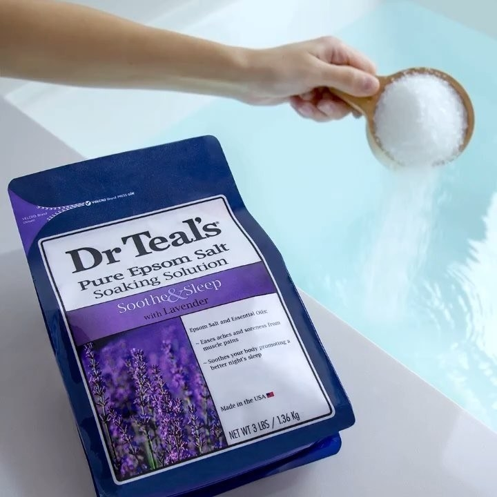 A person pours a cup of Epsom salts into a bath