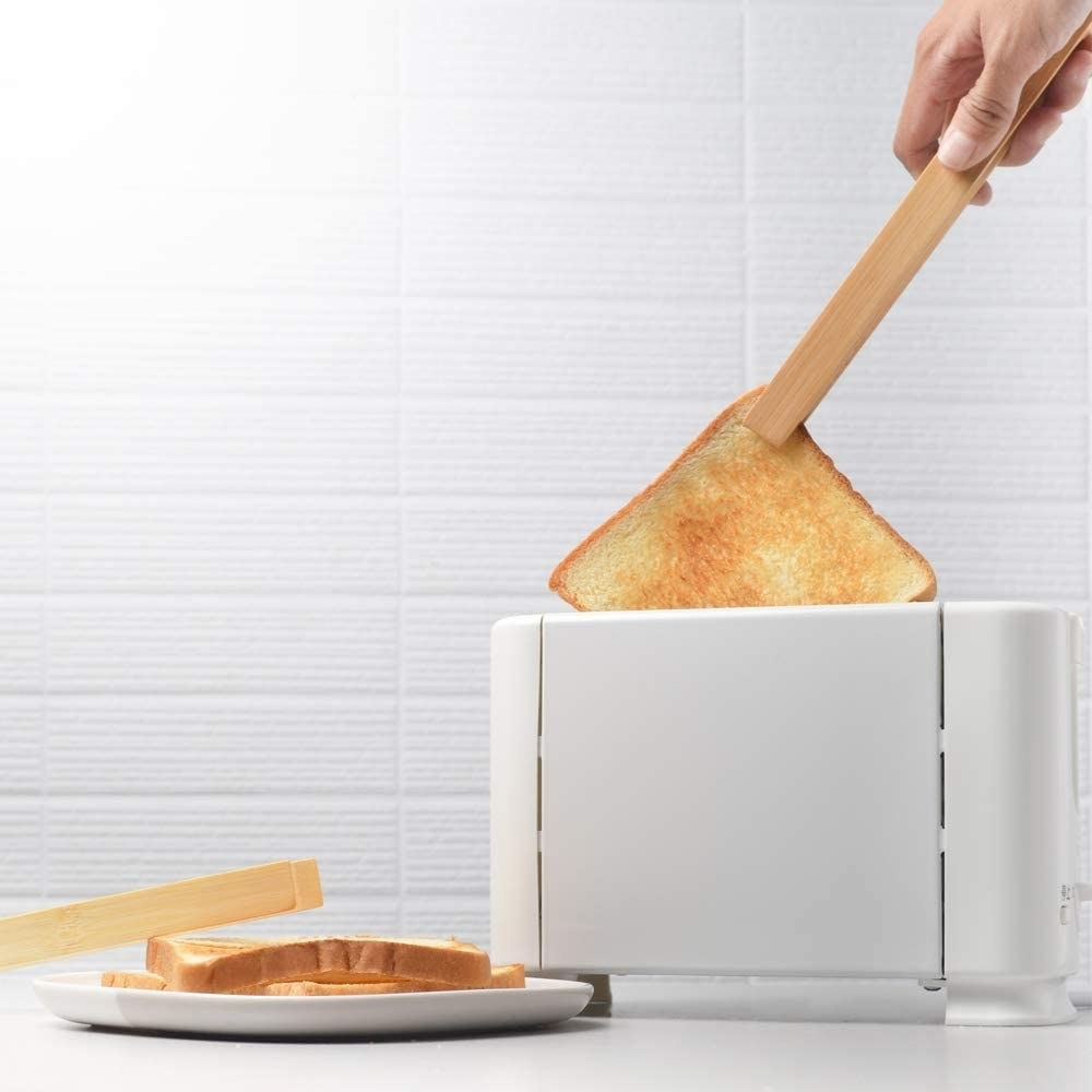 A person uses the tongs to lift hot toast out of the toaster