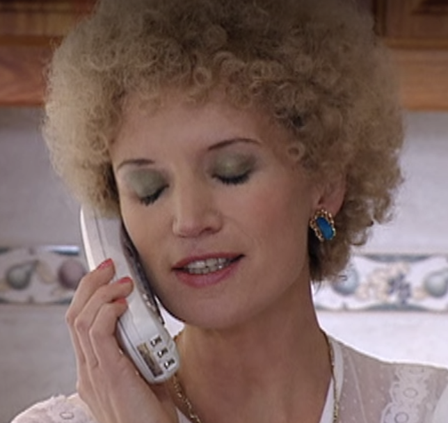 Kath talking on the phone while showing off her bright blue studs gilded in gold