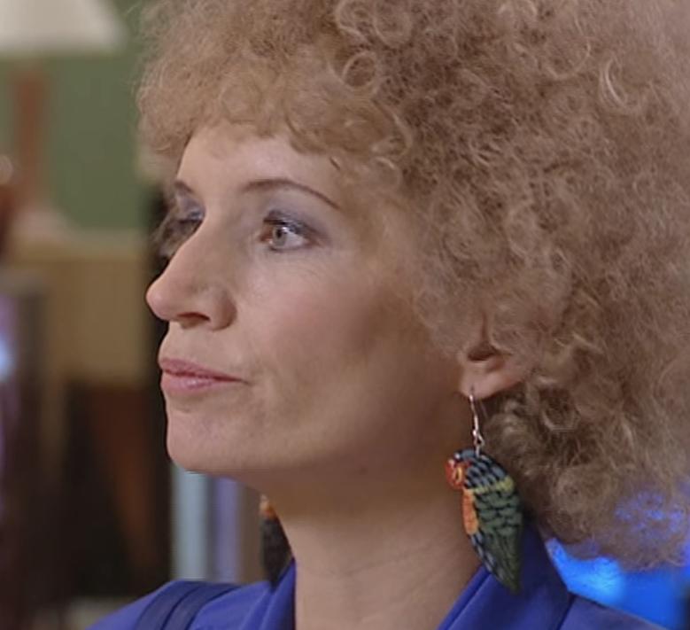 Kath wearing plastic rainbow lorikeet earrings that reach down to her shoulders