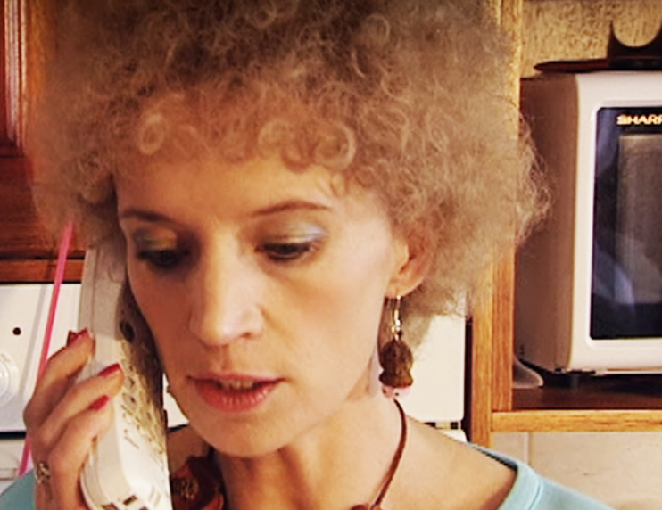 Kath talking on the phone wearing dangly earrings that look like gumnuts with eyes