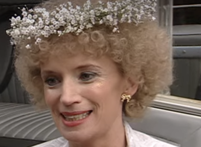 Kath is wearing tiny gold bows on her ears and a flower garland of little white flowers