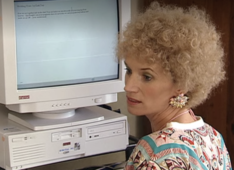 Kath in front of an extremely old computer wearing earrings that look like a clump of pearls glued together