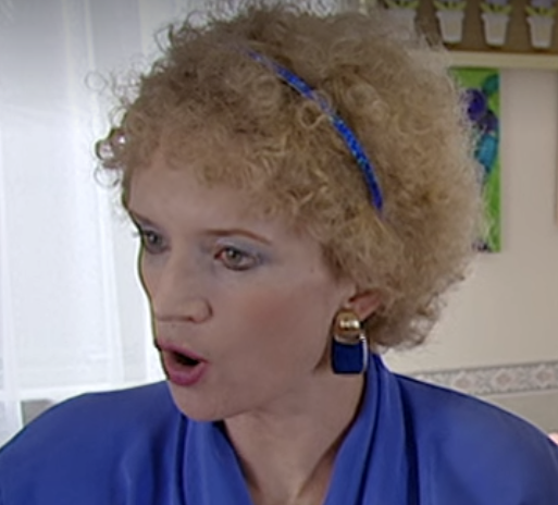 Big square blue earrings that match Kath's shirt, headband and eyeshadow