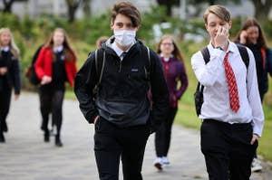 A teenage boy wears a mask as he walks among mask-less classmates