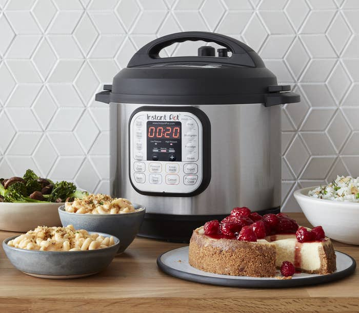 The Instant Pot on a counter with food items that can also be made inside like mac and cheese and cheesecake