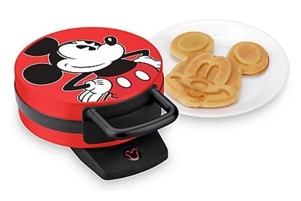 The Mickey waffle iron next to a plate holding a Mickey waffle